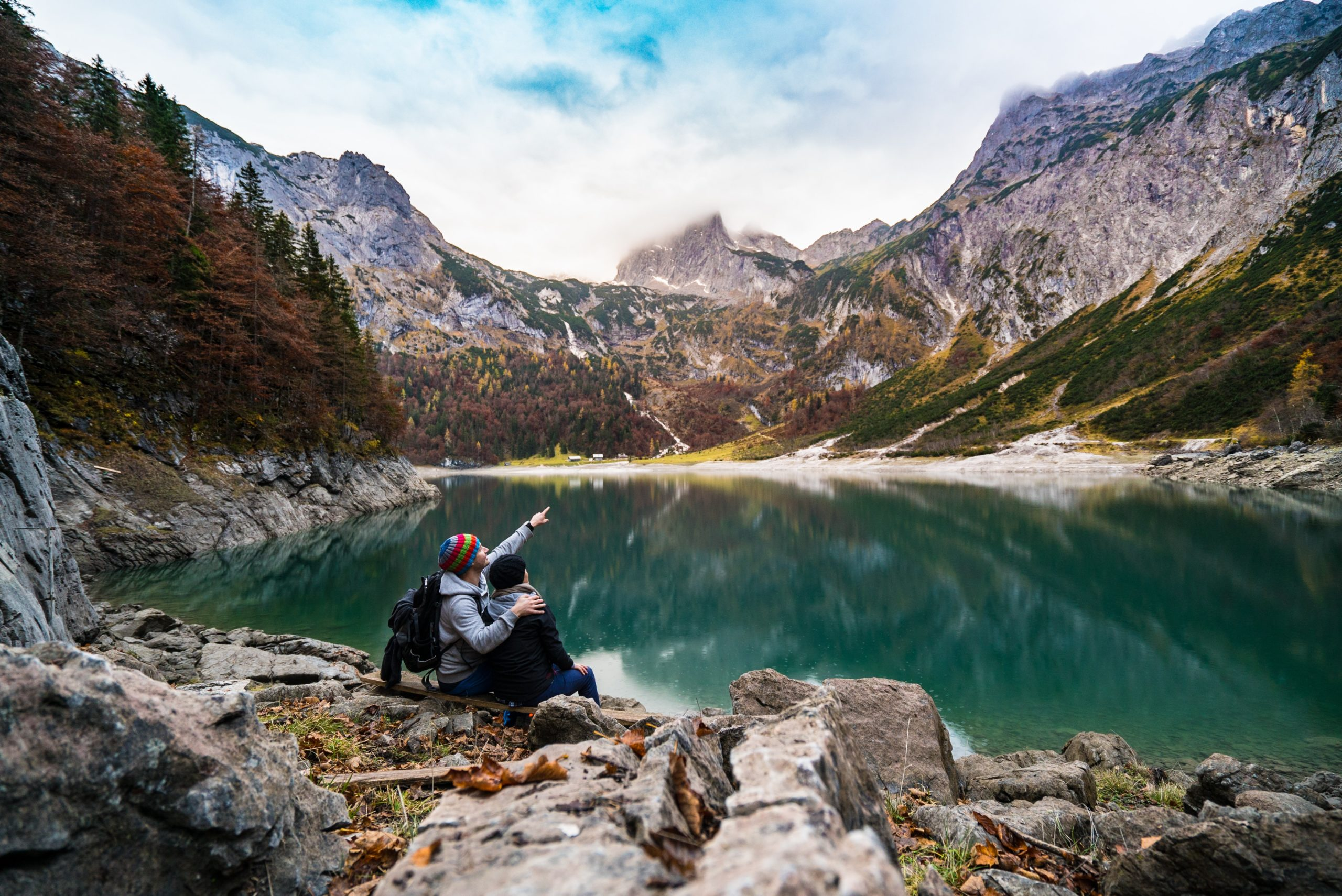 Couple sitting by a tourquoise lake
